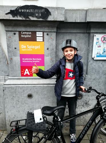Een jongen staat met zijn fiets voor het uithangbord van De Spiegel. Hij steekt een duim in de lucht en kijkt lachend in de camera. Op zijn fiets is een sensorbox bevestigd.