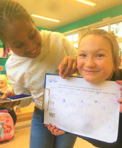 Twee meisjes tonen trots hun ingevuld enquêteformulier.
